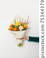 Spring yellow and orange tulips and white daffodils flowers in hand on white background 75344379