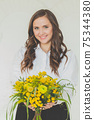 Cute brunette woman with yellow flowers on white background 75344380