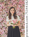 Happy cheerful woman with flowers on floral blossom background 75344382