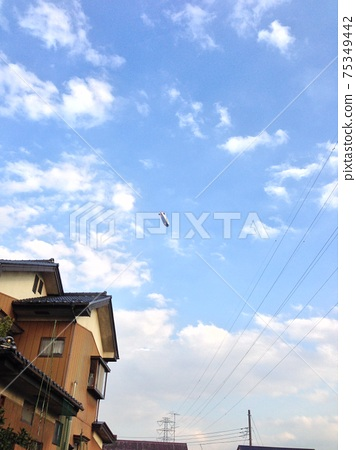 Photographing an airship flying over a residential area from the ground 75349442