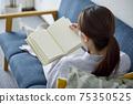 女人在客廳裡放鬆和看書 75350525