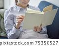 女人在客廳裡放鬆和看書 75350527