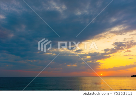 dynamic cloudscape in summer at sunrise. dark clouds on the sky in yellow and pink morning light. dramatic weather condition, picturesque scenery above the sea 75353513