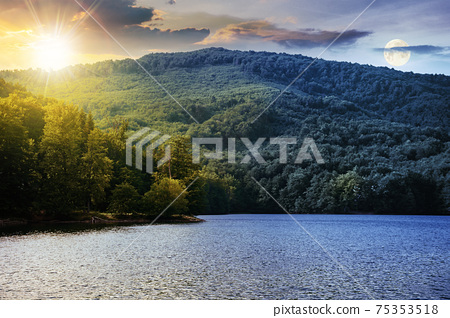 day and night time change concept on a lake among beech forest in summer. beautiful nature landscape in mountains. vihorlat national park with sun and moon on the sky 75353518