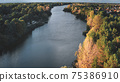 Cityscape at river shore aerial. Autumn nobody nature landscape. Colorful leafy trees forest sun day 75386910