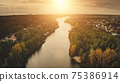 Sunset river aerial. Nobody nature landscape. Cottages at cityscape street. Urban building at shore 75386914