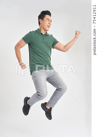Full-length photo of funny man 30s in casual t-shirt and jeans running or jumping in air isolated over white background 75412911