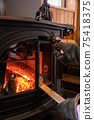 A photo of putting firewood in a wood stove (fireplace) 75418375
