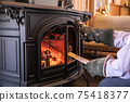 A photo of putting firewood in a wood stove (fireplace) 75418377