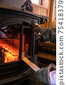 A photo of putting firewood in a wood stove (fireplace) 75418379