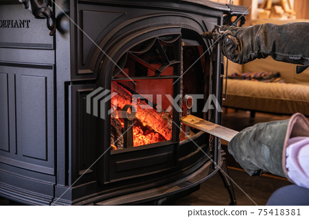 A photo of putting firewood in a wood stove (fireplace) 75418381