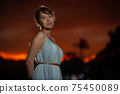 Half-woman waist-up standing in the park at dusk 75450089