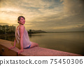 A lovely half-woman standing in the Cairns Lagoon at sunset 75450306
