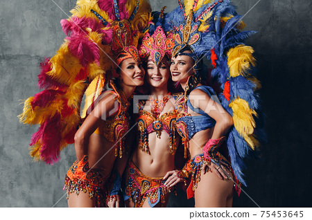 Three Woman in brazilian samba carnival costume with colorful feathers plumage 75453645