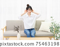 A young woman sitting on a sofa by the window and listening 75463198