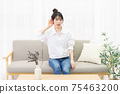 A young woman sitting on a sofa by the window and listening 75463200