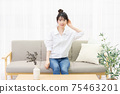 A young woman sitting on a sofa by the window and listening 75463201