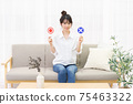 Young woman sitting on the couch by the window and holding an OK and NG placard 75463322