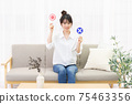 Young woman sitting on the couch by the window and holding an OK placard 75463356