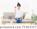 Young woman sitting on the couch by the window and holding an OK placard 75463357