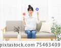 Young woman sitting on the couch by the window and holding an NG placard 75463409