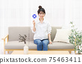 Young woman sitting on the couch by the window and holding an NG placard 75463411