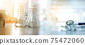 glass flask with text book and doctor stethoscope in medical lab banner background 75472060