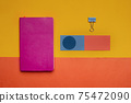 pink notebook with colorful blue orange paper on yellow colorful background 75472090