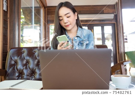 Asian female reading text message or social media on cell telephone during in modern cafe. 75482761