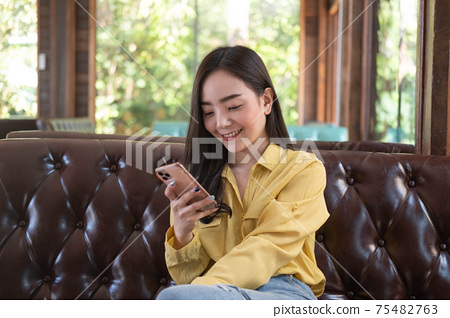 Asian female reading text message or social media on cell telephone during in modern cafe. 75482763