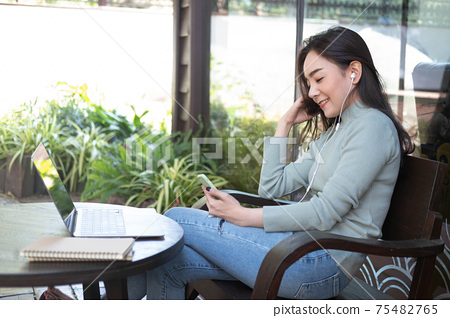 Happiness Asian woman listening music and using laptop at coffee shop. Relaxing time, 75482765