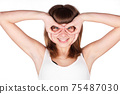 Young woman makes glasses with fingers. The girl looks in impromptu glasses, hand gesture. Isolated 75487030