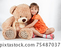 Cute little girl playing with her friend big fur bear. 75487037