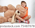 Cute little girl playing with her friend big fur bear. 75487078