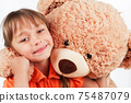 Cute little girl playing with her friend big fur bear. 75487079