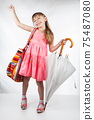 Cute little girl with umbrella and bag on her shoulder posing on a white background. 75487080
