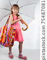 Cute little girl with umbrella and bag on her shoulder posing on a white background. 75487081