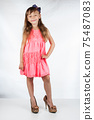 Cute little girl in high-heeled shoes posing on a white background. 75487083