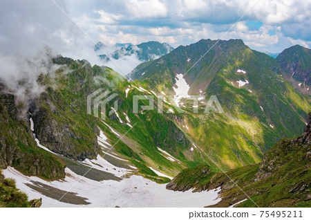 fagaras mountain landscape in summer. wonderful nature scenery with clouds on the peaks and snow in the valley. hills in grass and rocks. discover carpathins of romanian concept 75495211