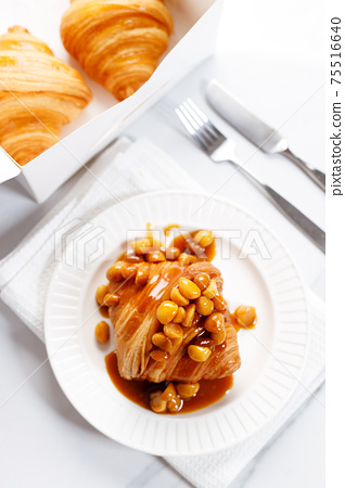 Fresh baked croissant on white plate 75516640