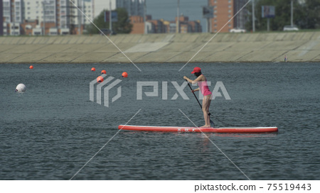 Athlete on stand up paddleboard sup holding paddle board up paddleboarding race. SUP surfboard. 75519443