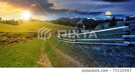 day and night time change concept above rural landscape in spring. path through grassy field. wooden fence on rolling hills. snow capped ridge in the distance. wonderful countryside scenery with sun 75520487