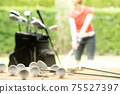 Golf balls, golf equipment, and golf club on a table on driving range with the golfer in background 75527397