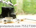 Golf balls and golf club and coffee cup on the table on driving range background 75527399