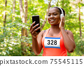 female marathon runner with headphones and phone 75545115