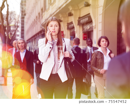 Young business woman talking on phone outdoors 75547452