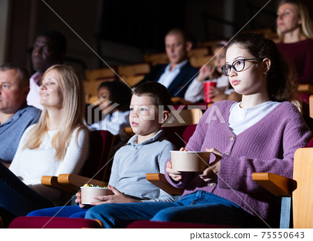Teen girl with family watching film in movie theater 75550643