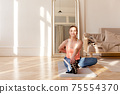 Sportswoman stretching body during training at home 75554370