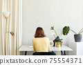 Unrecognizable woman sitting at table with flowers at home 75554371