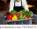 Crop cook with assorted vegetables on tray in restaurant 75556271